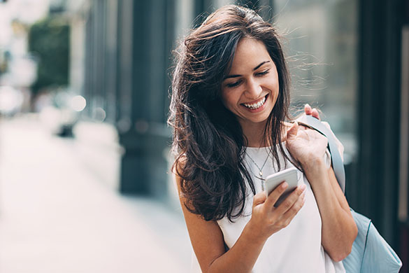 woman looking at her phone on the street (Flexible Banking for Your Busy Life)